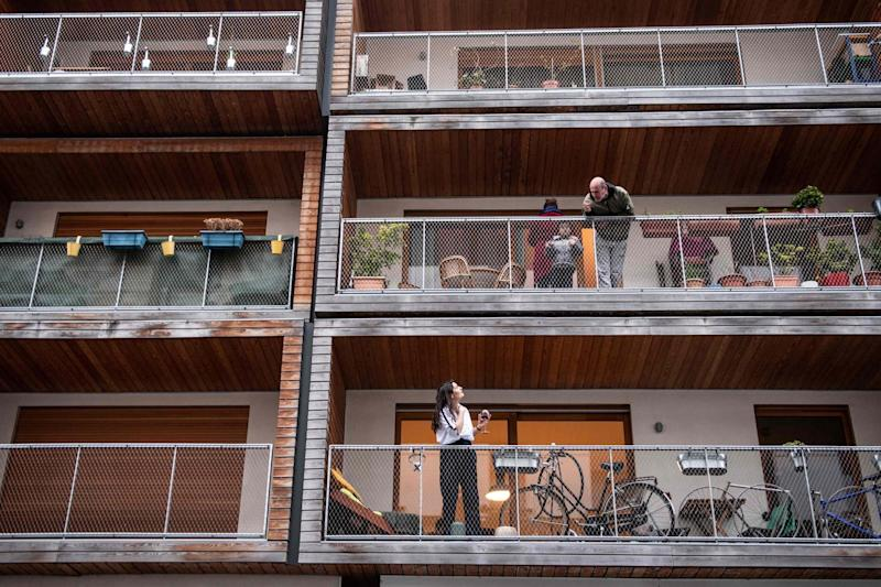 Neighbors talk to each other from their balconies in Paris: AFP via Getty Images