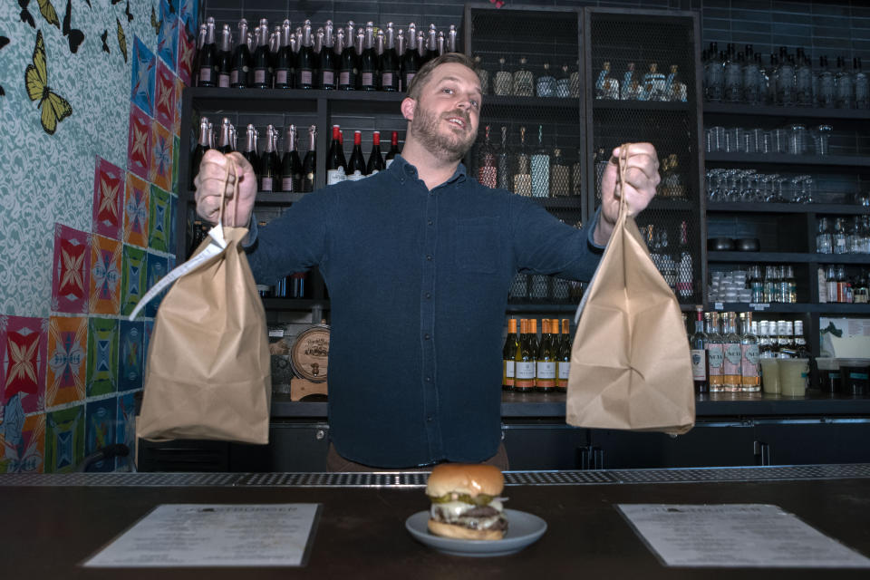 Josh Phillips, the co-owner of Espita, a stylish Mexican restaurant, displays a Ghostburger at his restaurant in downtown Washington, Monday, Feb. 15, 2021. Phillips opened a delivery-only brand called Ghostburger in August to keep Espita's kitchen running through the winter. He chose burgers because he wanted to reach new customers at a lower price point than Espita. It's been so successful that Phillips is now scouting for locations for standalone Ghostburger restaurants. (AP Photo/Jose Luis Magana)