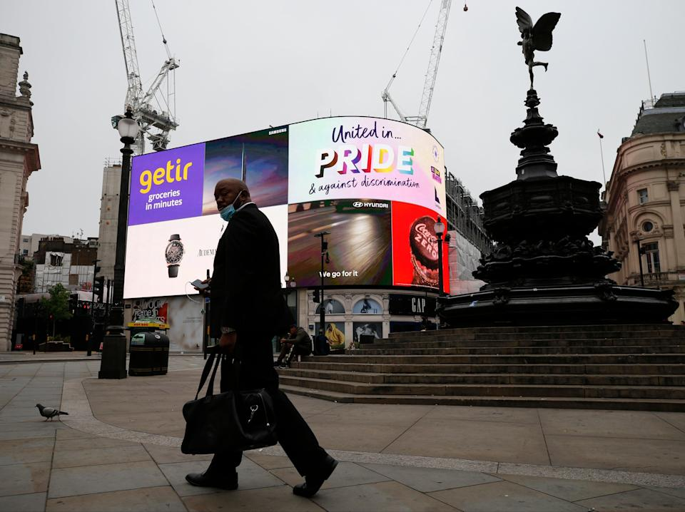 One man and his pigeon: an almost deserted Piccadilly Circus in central London on Sunday (Getty)
