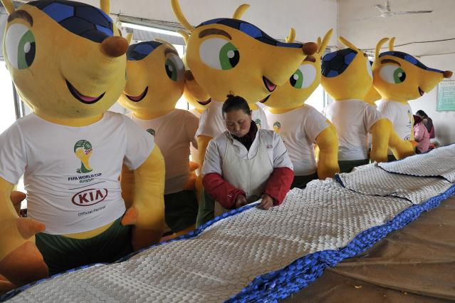 An employee works in front of newly made giant dolls of Fuleco the Armadillo, the official mascot of the FIFA 2014 World Cup, at a factory in Tianchang, Anhui province January 6, 2014. The 2014 World Cup will be held in Brazil from June 12 through July 13. REUTERS/Stringer (CHINA - Tags: SOCIETY SPORT SOCCER WORLD CUP)