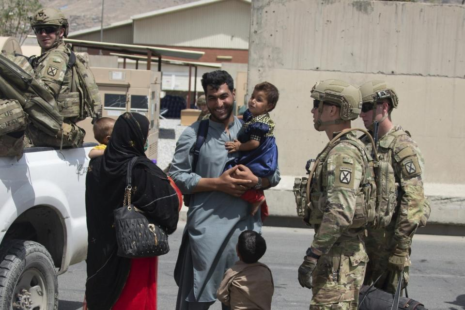 In this image provided by the U.S. Marine Corps, soldiers with the 10th Mountain Division escort evacuees at Hamid Karzai International Airport in Kabul, Afghanistan, Friday, Aug. 20, 2021. (Cpl. Davis Harris/U.S. Marine Corps via AP)