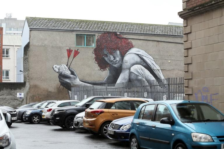 "Work in Belfast by French artist MTO, ""The Son of Protagoras,"" of a child holding a dove killed by two arrows, one representing Catholicism, the other Protestantism"