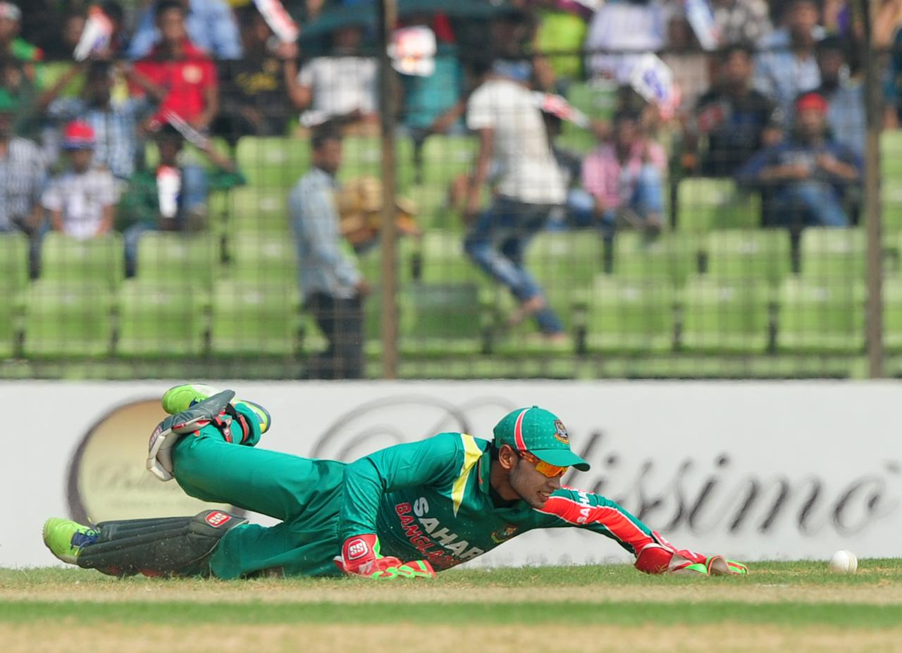 Bangladesh captain Mushfiqur Rahim attempts a catch during the third One-Day International (ODI) cricket match between Bangladesh and New Zealand at Khan Jahan Ali Stadium in Fatullah, on the outskirts of Dhaka on November 3, 2013.  AFP PHOTO/ Munir uz ZAMAN        (Photo credit should read MUNIR UZ ZAMAN/AFP/Getty Images)