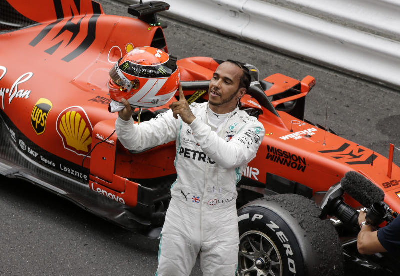 Mercedes driver Lewis Hamilton of Britain holds his red helmet to tribute Niki Lauda after he won the Monaco Formula One Grand Prix race, at the Monaco racetrack, in Monaco, Sunday, May 26, 2019. (AP Photo/Luca Bruno)