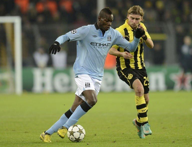 Manchester City striker Mario Balotelli (L) and Dortmund defender Marcel Schmelzer fight for the ball during their UEFA Champions League Group D football match in Dortmund. English champions City failed to save some face on Tuesday and qualify at least for the Europa League by putting up a limp performance in a 1-0 defeat