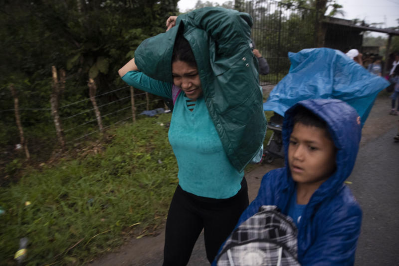 "Honduran migrants cover themselves from the rain during their journey toward the distant United States, in Entre Rios, Guatemala, Thursday, Jan. 16, 2020. Less-organized migrants, tighter immigration control by Guatemalan authorities and the presence of U.S. advisers have reduced the likelihood that the hundreds of migrants who departed Honduras will form anything like the cohesive procession the term ""caravan"" now conjures. (AP Photo/Moises Castillo)"