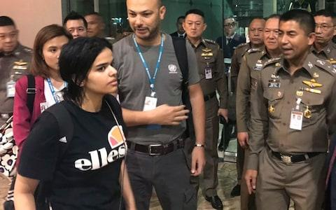Rahaf Mohammed Alqunun walks by Chief of Immigration Police Surachate Hakparn in an image released by the immigration bureau