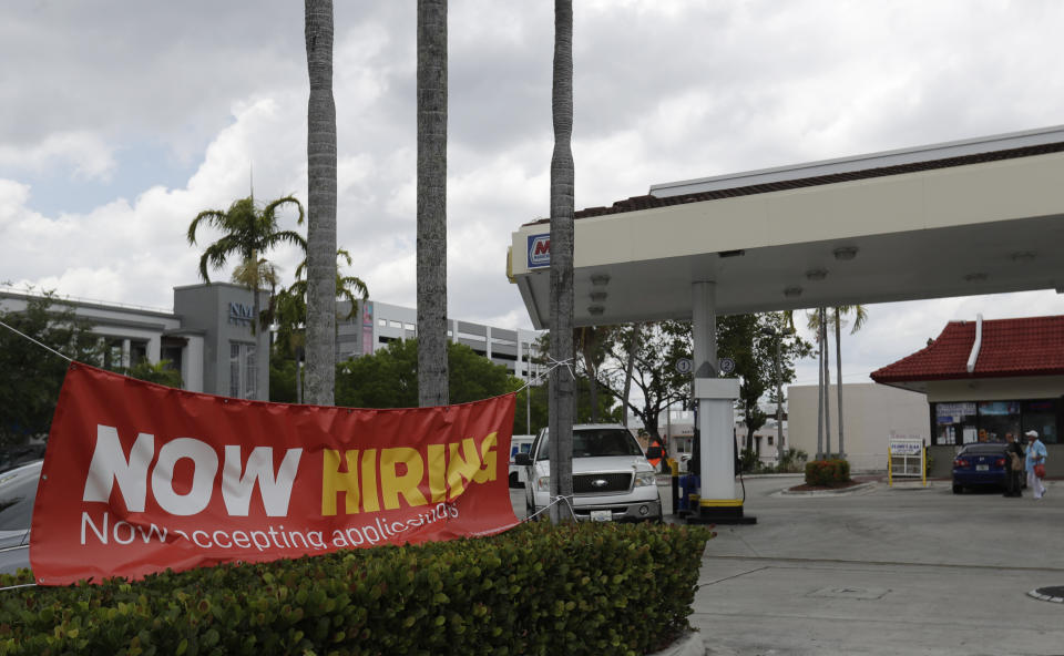 In this, Wednesday, May 6, 2020 photo, a now hiring sign is displayed on a street corner in North Miami Beach, Fla. Initial jobless claims in Florida dropped by more than half last week compared to the prior week, according to figures released Thursday, as unemployed Floridians continued facing problems signing up and receiving benefits because of difficulties with a computer system. (AP Photo/Wilfredo Lee)