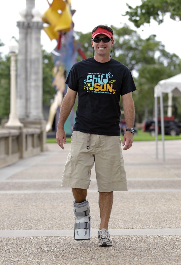 In this photo taken Thursday, April 19, 2012, Greg Farris walks while wearing a protective boot as he helps set up for a weekend triathlon event in Lakeland, Fla. Farris injured his foot while running in barefoot running shoes.(AP Photo/John Raoux)