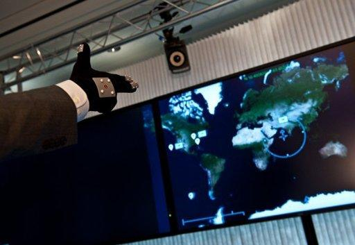 """An employee demonstrates the use of a data glove to navigate a map on a computer screen at Los Angeles-based software company Oblong Industries' offices in Washington in June 2012. The software behind the film """"Minority Report"""" -- where Tom Cruise speeds through video on a large screen using only hand gestures -- is making its way into the real world"""