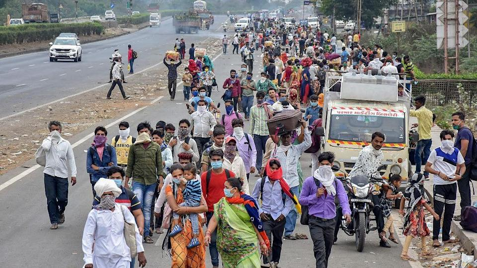 Migrant workers walk back to their villages from Surat on 27 March 2020.