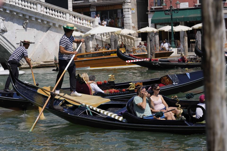 Tourists enjoy a Venetian gondola tour, in Venice, Italy, Thursday, June 17, 2021. After a 15-month pause in mass international travel, Venetians are contemplating how to welcome visitors back to the picture-postcard canals and Byzantine backdrops without suffering the indignities of crowds clogging its narrow alleyways, day-trippers perched on stoops to imbibe a panino and hordes of selfie-takers straining for a spot on the Rialto Bridge or in front of St. Mark's Basilica. (AP Photo/Luca Bruno)