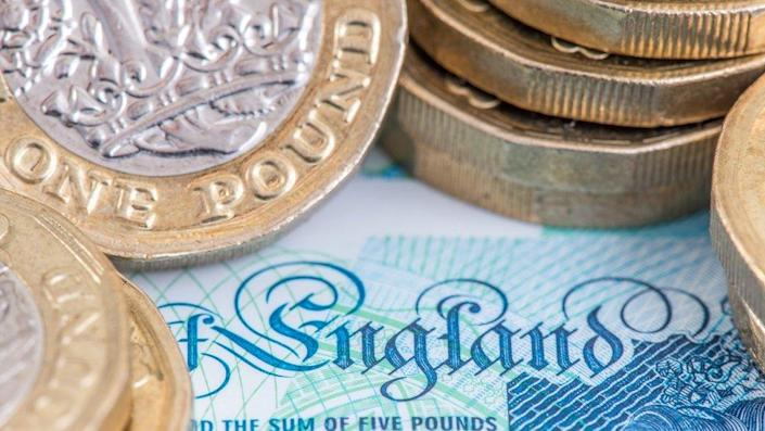 """The word """"England"""" as depicted on an English £5 note, surrounded by stacks of newly minted pound coins"""