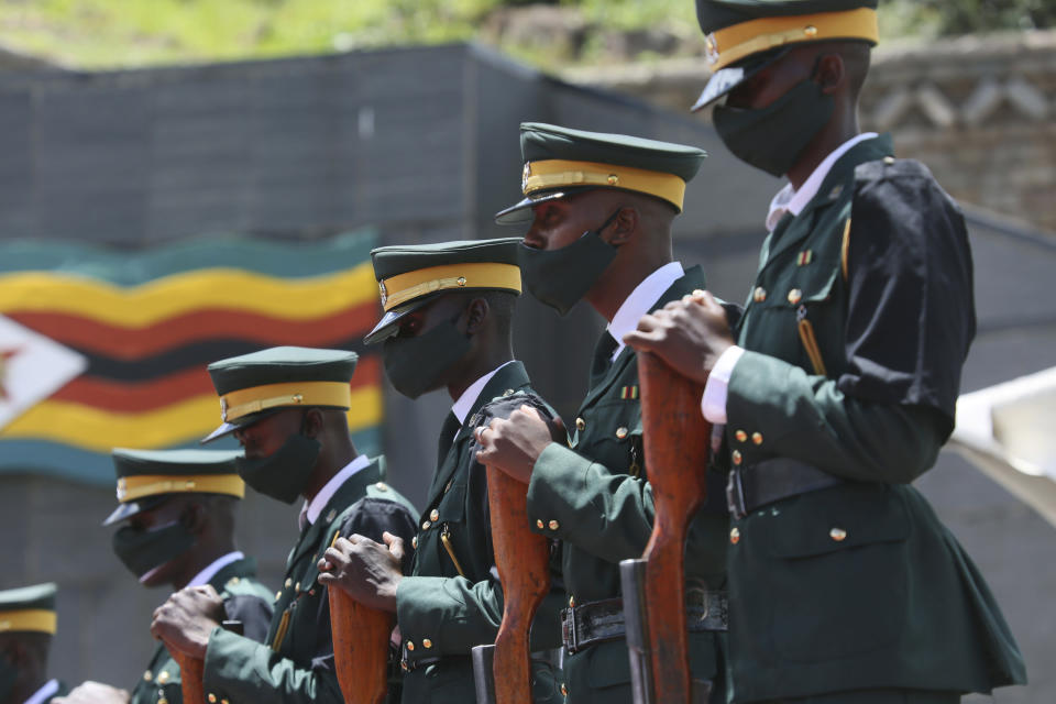 Soldiers stand guard at the burial of three top government officials, at the National Heroes Acre in Harare, Wednesday, Jan,.27, 2021. Zimbabwe on Wednesday buried three top officials who succumbed to COVID-19, in a single ceremony at a shrine reserved almost exclusively for the ruling elite as a virulent second wave of the coronavirus takes a devastating toll on the country. (AP Photo/Tsvangirayi Mukwazhi)