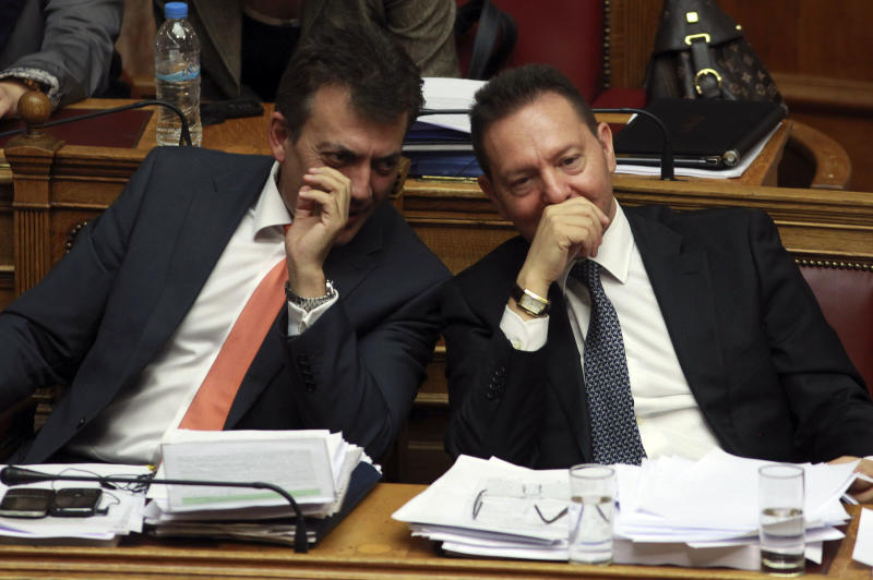 Greece's Finance Minister Yannis Stournaras, right, and Labour Minister Yiannis Vroutsis speak to each other during a parliament meeting, in Athens, Wednesday, Nov. 7, 2012. Greece's fragile coalition government faces its toughest test so far when lawmakers vote late Wednesday on new painful austerity measures demanded to keep the country afloat, on the second day of a nationwide general strike. (AP Photo/Thanassis Stavrakis)