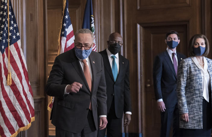 On the first full day of the Democratic majority in the Senate, Majority Leader Chuck Schumer, D-N.Y., left, is joined by Sen. Raphael Warnock, D-Ga., center, and Sen. Jon Ossoff, D-Ga., with Sen. Catherine Cortez Masto, D-Nev., who chaired the Democratic Senatorial Campaign Committee, far right, at the Capitol in Washington, Thursday, Jan. 21, 2021. The pivotal Georgia runoff election this month was decisive in handing Democrats the majority in the Senate. (AP Photo/J. Scott Applewhite)