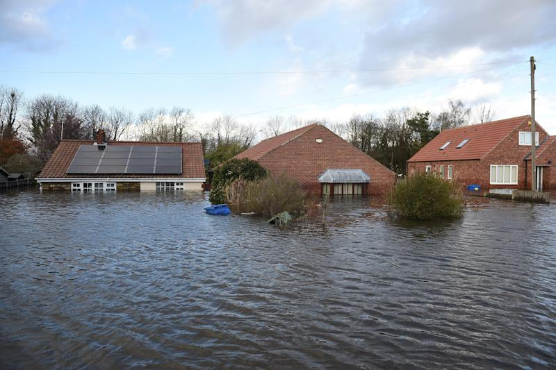 Flood water surrounds houses and residential properties in Snaith, northern England on March 1, 2020 after Storm Jorge brought more rain and flooding to parts of the UK. - Following storms Ciara, Dennis and now Jorge, the record for the UK's wettest February on record has now been broken, with an 202.1 rain last month, beating February 1990 when 193.4mm fell, the Met Office reported on Sunday. (Photo by Oli SCARFF / AFP) (Photo by OLI SCARFF/AFP via Getty Images)