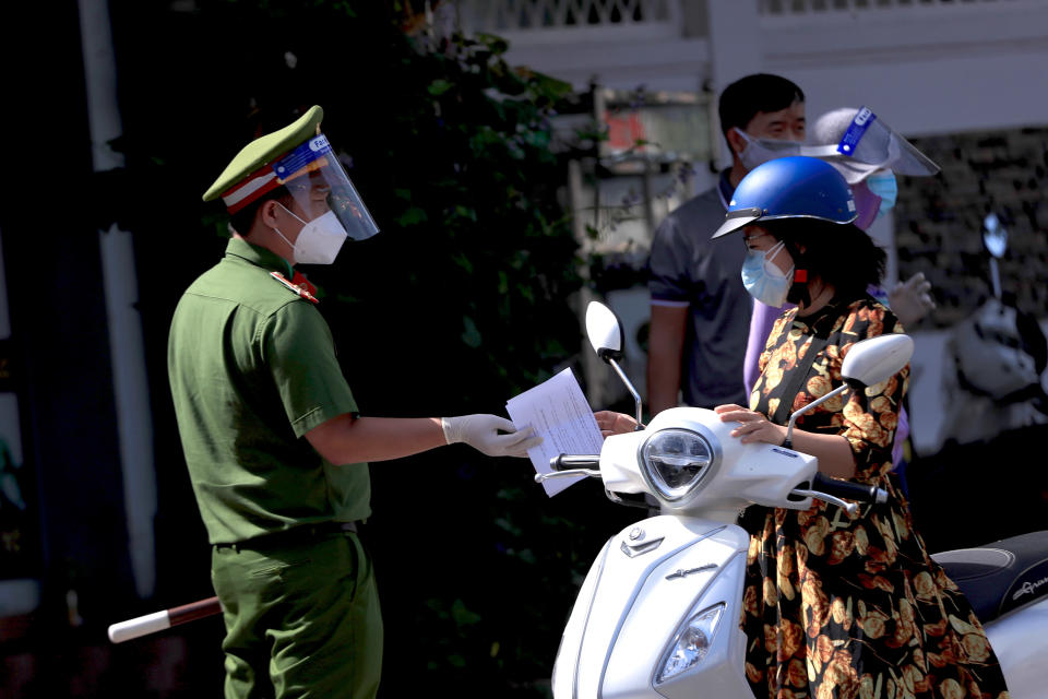 A policeman hands back the travel permit to a commuter after checking at a street checkpoint in Vung Tau, Vietnam on Monday, Sept. 6, 2021. Over 20 million Vietnamese students start a new school year on Monday, many of them on virtual classrooms as more than half of the country is in lockdown to contain a COVID-19 surge. (AP Photo/Hau Dinh)