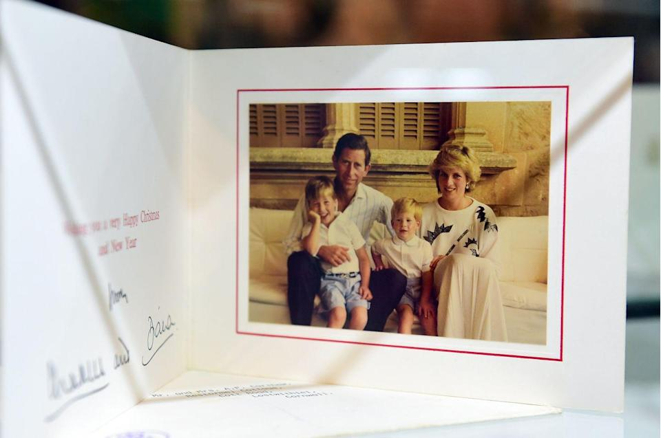 <p>This sweet photo sees the couple in matching white ensembles, with William leaning on his father's knee and Harry sitting between his parents. In the snap, Diana wears a white maxi dress with a green pattern. </p>