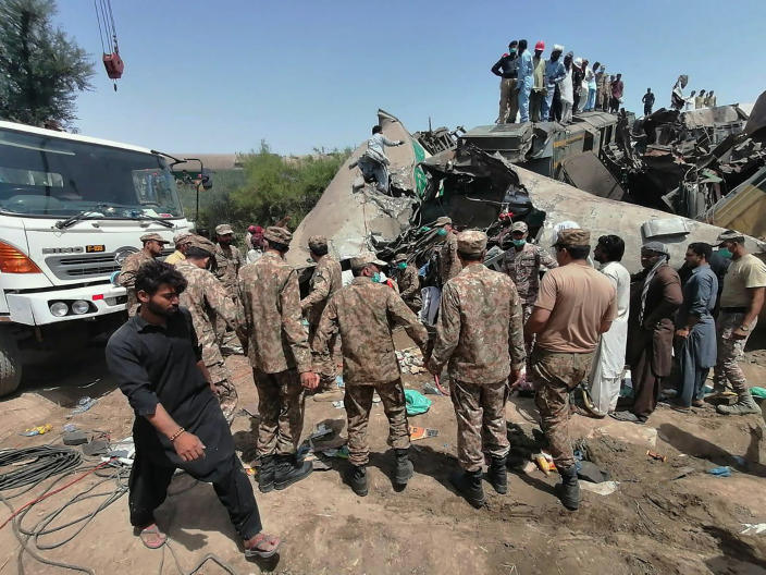 In this photo released by Pakistan's army media wing Inter Services Public Relations, troops and rescue workers gather at the site of trains collided in Ghotki district in the southern Pakistan, Monday, June 7, 2021. Two express trains collided in southern Pakistan early Monday, killing dozens of passengers, authorities said, as rescuers and villagers worked to pull injured people and more bodies from the wreckage. (Inter Services Public Relations vis AP)