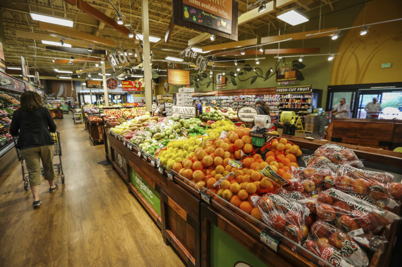 FILE - In this May 25, 2017, file photo, shoppers make their way around the new produce section in the newly-expanded City Market in Eagle, Colo. The supermarket is one of the most important places to be shopping-savvy. The good news is that there are so many easy and effective way to slash your grocery budget. Buy whole fruits and vegetables. Pound for pound, whenever you buy anything that has been peeled, cut up, or prepped in any way you are paying a premium. (Chris Dillmann/Vail Daily via AP, File)