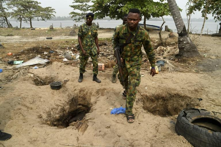The ground is pockmarked with holes where residents have dug down to pipelines, some filled with shiny oil and water (AFP Photo/PIUS UTOMI EKPEI)