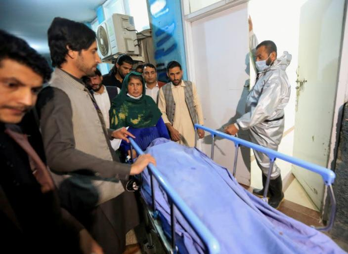 FILE PHOTO: Afghan men transport the body of one of three female media workers who were shot and killed by an unknown gunmen, at a hospital in Jalalabad