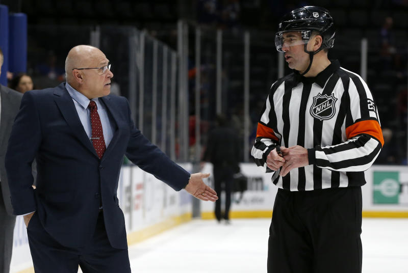 New York Islanders head coach Barry Trotz has words with referee Marc Joannette after video review confirmed an overtime goal scored by the Carolina Hurricanes after an NHL hockey game, Saturday, March 7, 2020, in Uniondale, NY. (AP Photo/Jim McIsaac)