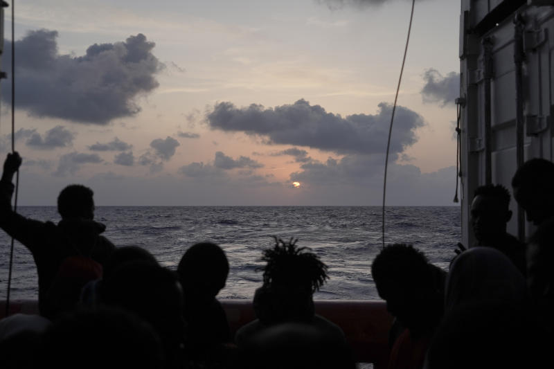 Migrants are silhouetted during the sunrise on the deck of the Ocean Viking as it sails in the Mediterranean Sea, Saturday, Sept. 21, 2019. The humanitarian ship operated by SOS Mediterranee and Doctors Without Borders is still waiting to be assigned a place of safety to disembark 182 people rescued after fleeing Libya. (AP Photo/Renata Brito)