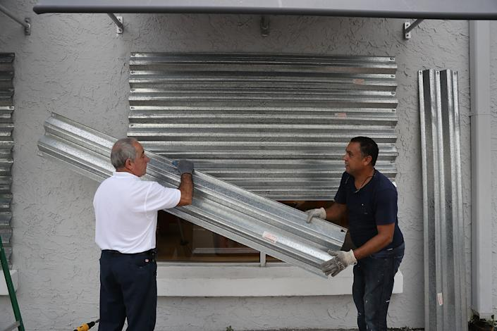 Gus Sousa and Winston Mora (L-R) put hurricane shutters on a business as they prepare for Hurricane Irma on September 6, 2017 in Miami.