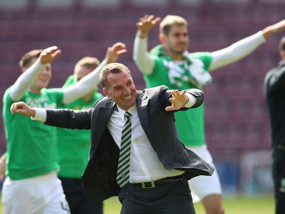 Brendan Rodgers celebrates with his players after the final whistle (Getty)