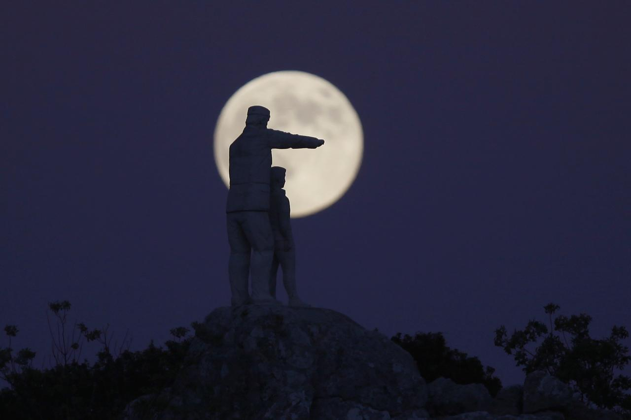 The statue of a man and a boy, a monument dedicated to forest rangers, is silhouetted against the supermoon as it rises at the Sierra de las Nieves (Mountain range of Snows) nature park and biosphere reserve between El Burgo and Ronda, near Malaga, southern Spain, August 10, 2014. Occurring when a full moon or new moon coincides with the closest approach the moon makes to the Earth, the supermoon results in a larger-than-usual appearance of the lunar disk. REUTERS/Jon Nazca (SPAIN - Tags: ENVIRONMENT SOCIETY)