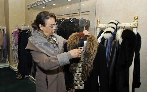 A woman holds a coat that once belonged to Leila Ben Ali, wife of ousted Tunisian dictator Zine El Abidine Ben Ali. Coats belonging to Leila Trabelsi, who was notorious for her expensive tastes, could fetch as much as 4,000 euros