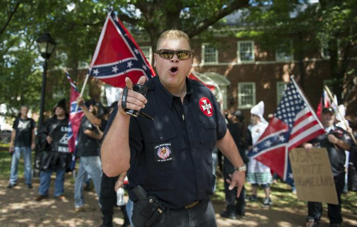 A man wearing white supremacist symbols and a holstered pistol points while several people stand behind him waving Confederate flags