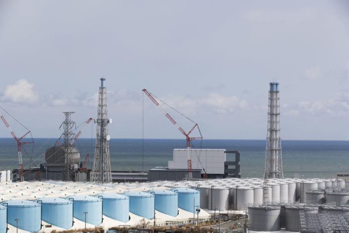 """FILE - In this Feb. 27, 2021, file photo, the Pacific Ocean looks over nuclear reactor units of No. 3, left, and 4 at the Fukushima Daiichi nuclear power plant in Okuma town, Fukushima prefecture, northeastern Japan. The Japanese government has decided to get rid of the massive amounts of treated but still radioactive water stored in tanks at the wrecked Fukushima nuclear plant by releasing it into the Pacific ocean, a conclusion widely expected but delayed for years amid protests and safety concerns. Prime Minister Yoshihide Suga on Wednesday, April 7, 2021, told top fisheries association officials that his government believes the release to sea is the most realistic option and a final decision will be made """"with days.""""(AP Photo/Hiro Komae, File)"""