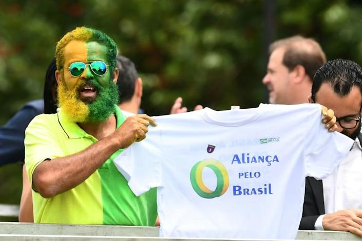 A supporter of Brazilian President Jair Bolsonaro holds a t-shirt during the launch of Bolsonaro's new party, the Alliance for Brazil, at a hotel in Brasilia (AFP Photo/EVARISTO SA)