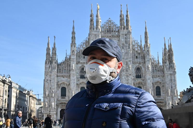 Un turista con una mascarilla en la piazza del Duomo, de Milán. (Photo: Getty)