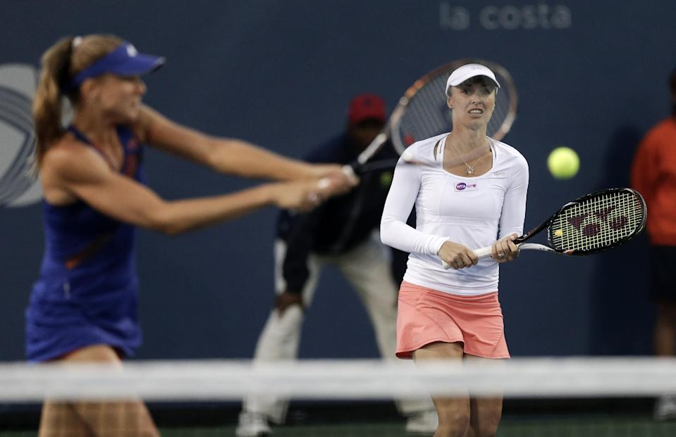 Martina Hingis, right, of Switzerland, watches playing partner Daniela Hantuchova, of Slovakia, hit during their doubles tennis match against Germany's Julia Goerges and Croatia's Darija Jurak at the Southern California Open tennis tournament Wednesday, July 31, 2013 in Carlsbad, Calif. (AP Photo/Chris Carlson)