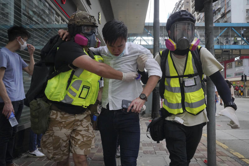 Medical volunteers help a man to move away as police fire teargas during a protest against Beijing's national security legislation in Causeway Bay in Hong Kong, Sunday, May 24, 2020. Hong Kong police fired volleys of tear gas in a popular shopping district as hundreds took to the streets Sunday to march against China's proposed tough national security legislation for the city. (AP Photo/Vincent Yu)