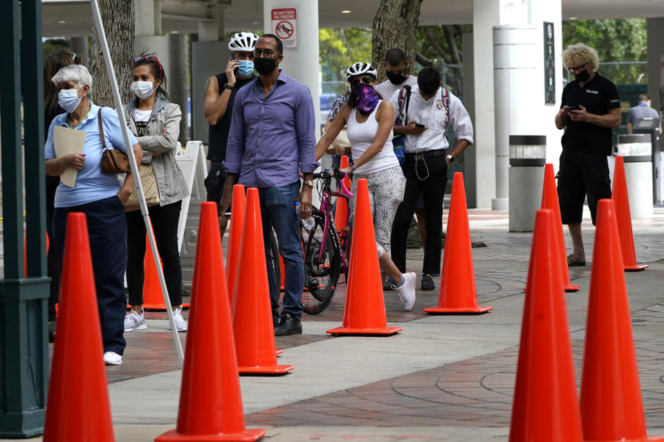 People wait in line at a walk-up COVID-19 testing site, Wednesday, Nov. 18, 2020, in Miami. Florida health officials have reported a steady increase in the number of new coronavirus cases each day over the past month and a half.(AP Photo/Lynne Sladky)