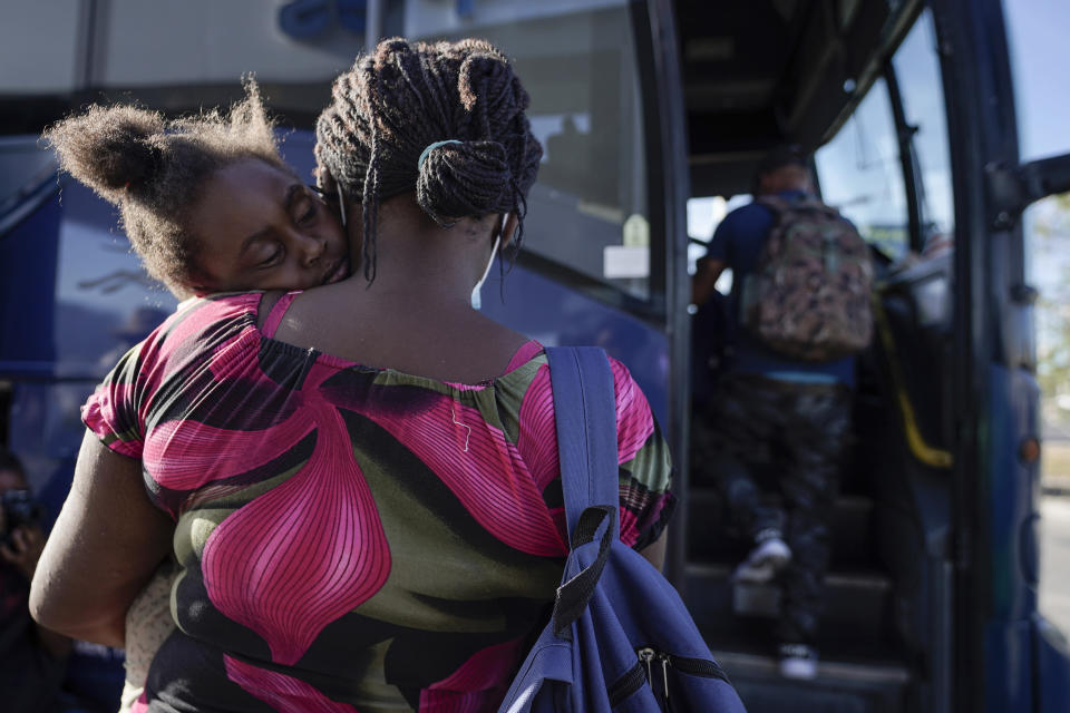 FILE - In this Wednesday, Sept. 22, 2021, file photo, a child sleeps on the shoulder of a woman as they prepare to board a bus to San Antonio moments after a group of migrants, many from Haiti, were released from custody upon crossing the Texas-Mexico border in search of asylum in Del Rio, Texas. On Friday, the camp on the U.S. side that once held as many as 15,000 mostly Haitian refugees was completely cleared. (AP Photo/Julio Cortez, File)