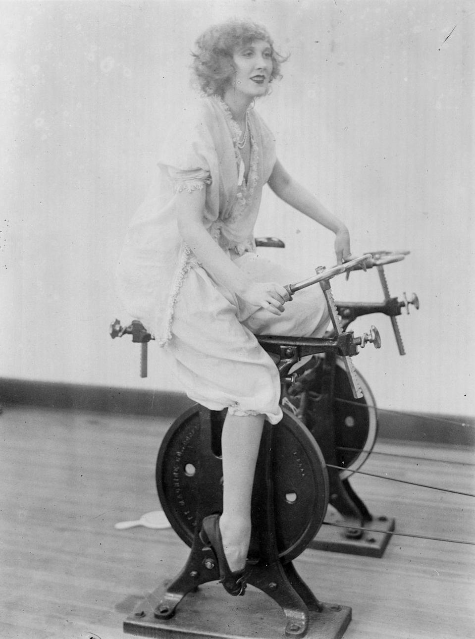"<p>Here's proof that cycling has been popular for a very long time: This is a photo from March 1921 featuring a woman on a stationary bike. Her outfit might look odd now, but back then, it was pretty <a href=""https://thevintagewomanmagazine.com/history-of-exercise-fashion/"" rel=""nofollow noopener"" target=""_blank"" data-ylk=""slk:standard"" class=""link rapid-noclick-resp"">standard</a> for women to wear outfits of ""leisure,"" and heels or loafers (Adidas sneakers weren't exactly a thing yet). <br></p>"