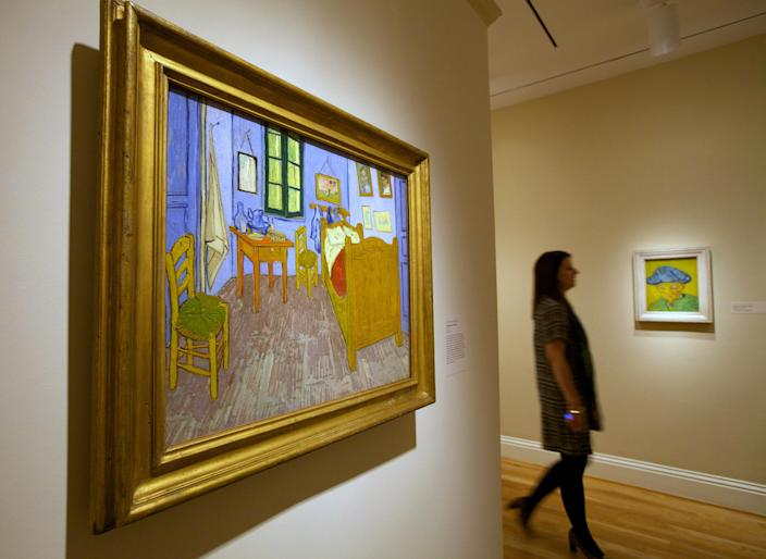 """In this Oct. 8, 2013 photo, a woman walks past Vincent van Gogh pieces, including """"Portrait of Camille Roulin,"""" right, and """"The Bedroom at Arles,"""" left, on display at The Phillips Collection in Washington. In the midst of the shutdown of federally funded museums, the private Phillips Collection is launching the first major exhibition of Vincent van Gogh's artwork in Washington in 15 years. (AP Photo/Molly Riley)"""