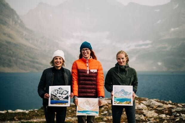Artists Kerry Langlois, left, Kayla Eykelboom and Emily Beaudoin show their original paintings at Lake McArthur in Yoho National Park, B.C. (@viktorianorth/Instagram - image credit)