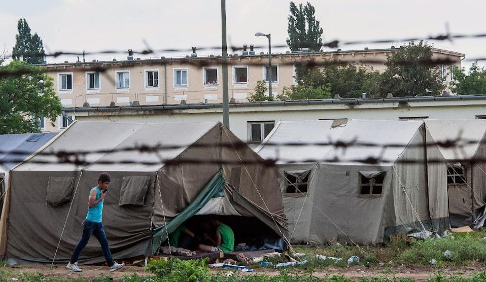 A refugee walks past a tent in a camp in Debrecen, Hungary on June 30, 2015 (AFP Photo/Steven Debora)