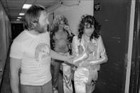 <p>Led Zeppelin's Jimmy Page and Robert Plant chat with a fan as they walk backstage at Madison Square Garden after a concert in 1977. </p>