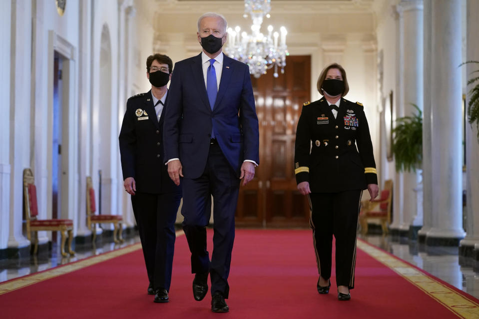 President Joe Biden walks with U.S. Air Force Gen. Jacqueline Van Ovost, left, and U.S. Army Lt. Gen. Laura Richardson before speaking at an event to mark International Women's Day, Monday, March 8, 2021, in the East Room of the White House in Washington. (AP Photo/Patrick Semansky)