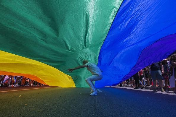 A man runs under a rainbow flag as it is carried in the 48th annual LA Pride Parade on June 10, 2018, in the Hollywood section of Los Angeles and West Hollywood, California. The annual gay rights event returns to its customary format of celebration following a one-time switch to the Resist March protest against Trump administration policies. LA Pride began on June 28, 1970, exactly one year after the historic Stonewall Rebellion in New York City. (Photo by David McNew/Getty Images)