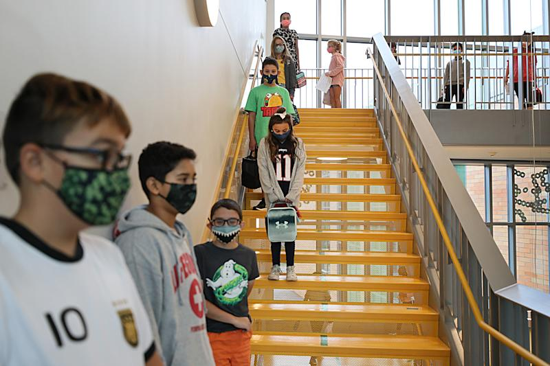 Masked children line up at a safe social distance before heading into a lunch room at Woodland Elementary School in Milford, MA on Sept. 11, 2020. (Suzanne Kreiter/The Boston Globe via Getty Images)