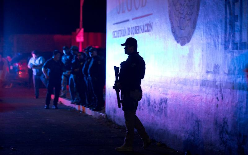 A police offer stands guard outside the detention centre from where 1,300 migrants escaped on Thursday night - AP